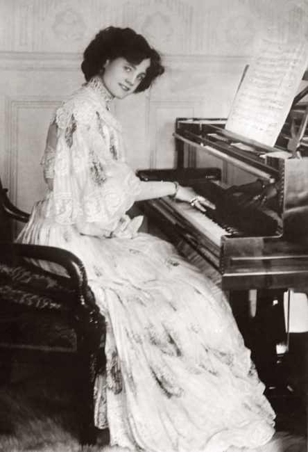 A woman playing piano in a vintage pic