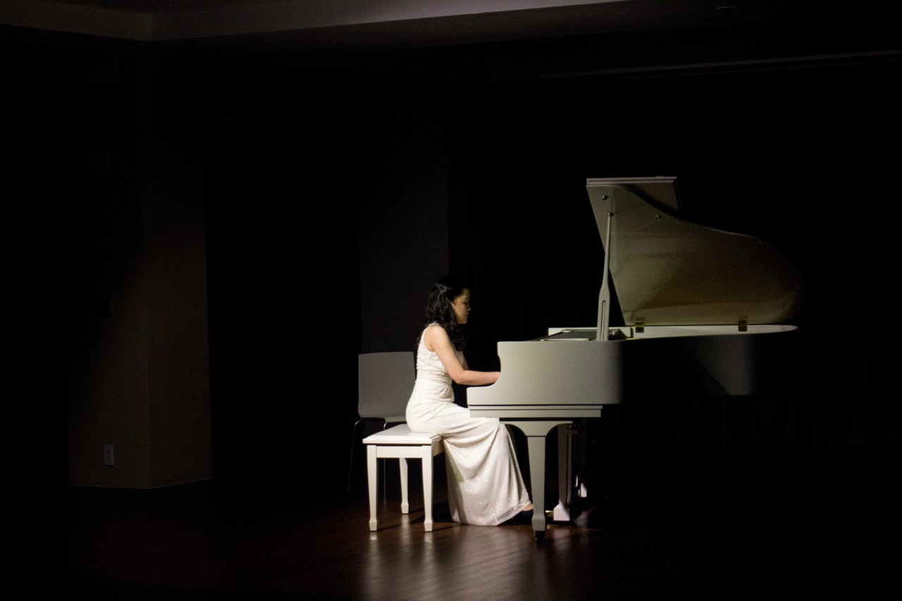 A girl on piano in a dark room
