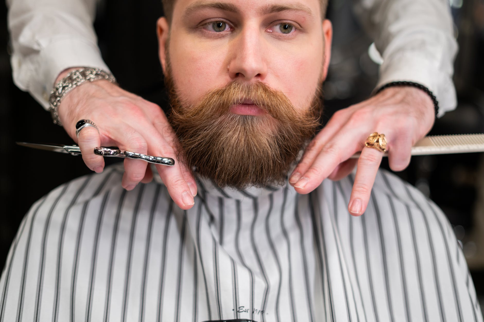 man in white and gray pinstripe having a haircut